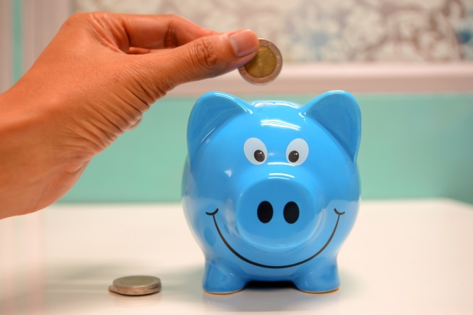 Dropping a toonie into a cute, blue, smiling pig piggy bank